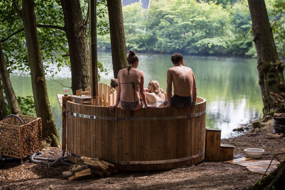 Young people sitting in hot-tubs outdoors